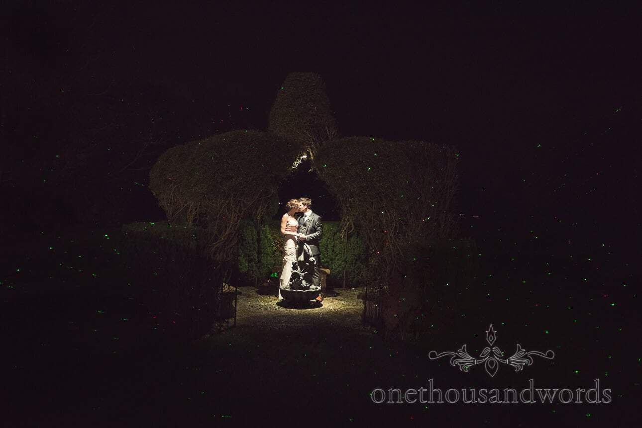 Bride and groom kissing at night in garden lit by lazers