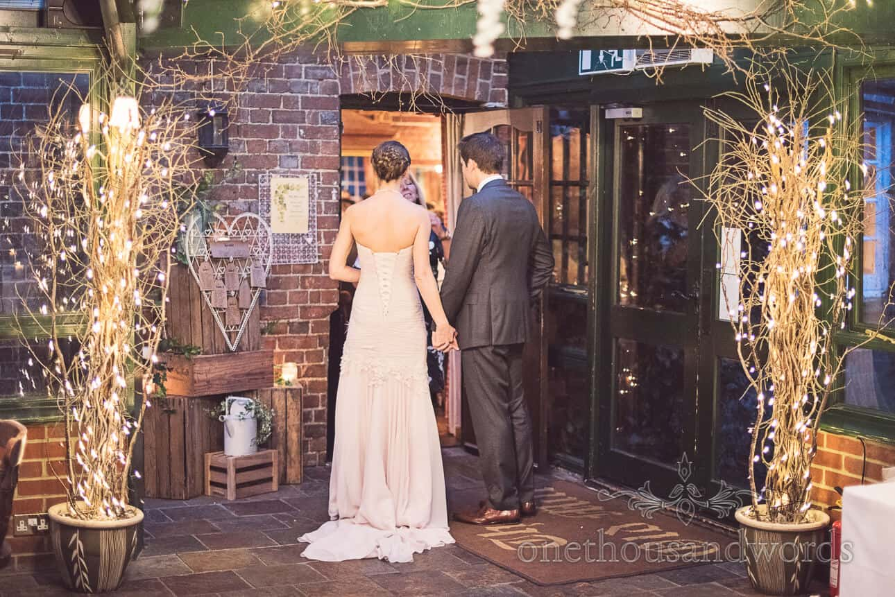Bride and groom wait hand in hand to enter their wedding breakfast