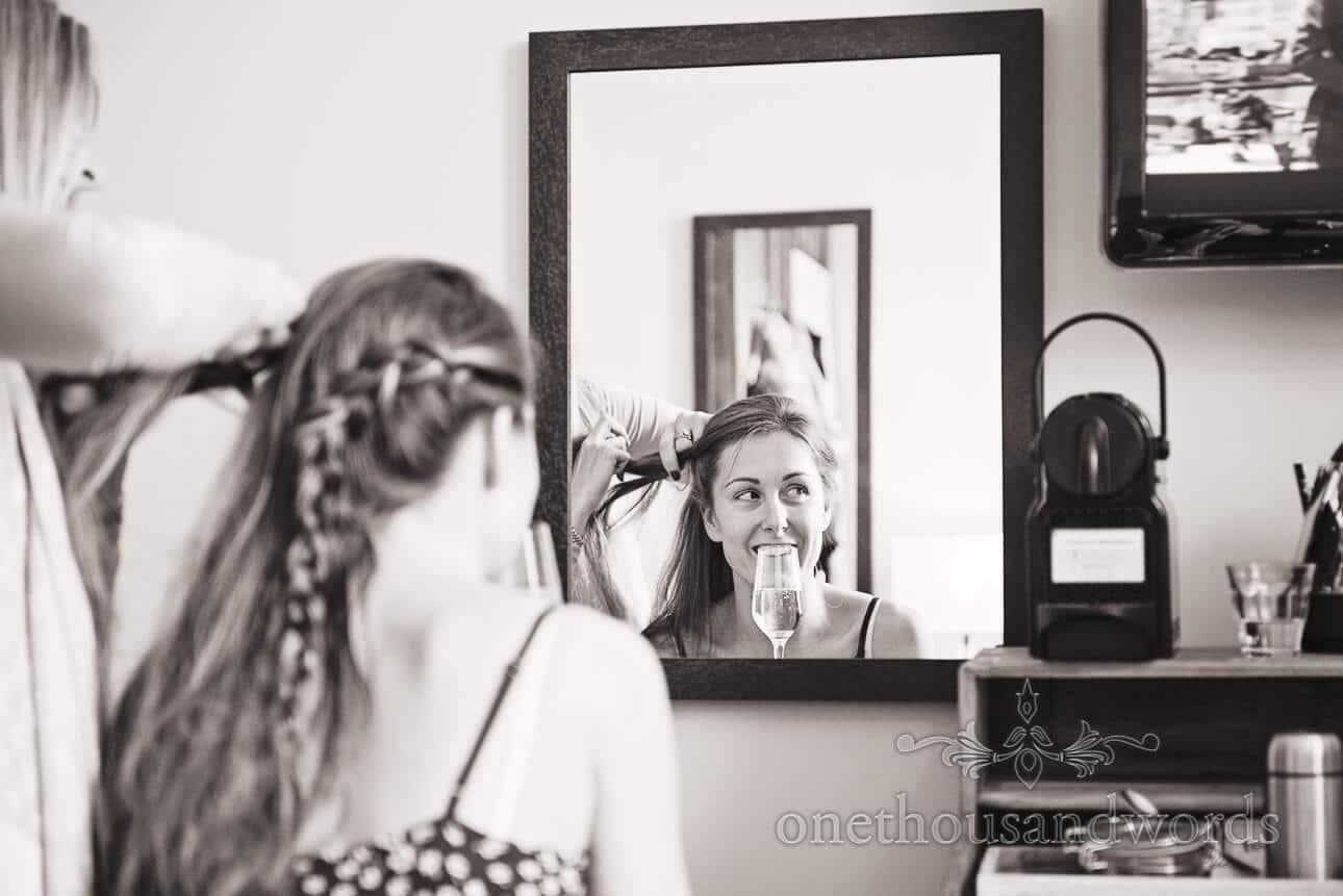 Bride has hair styled in mirror on wedding mornign in Berkshire