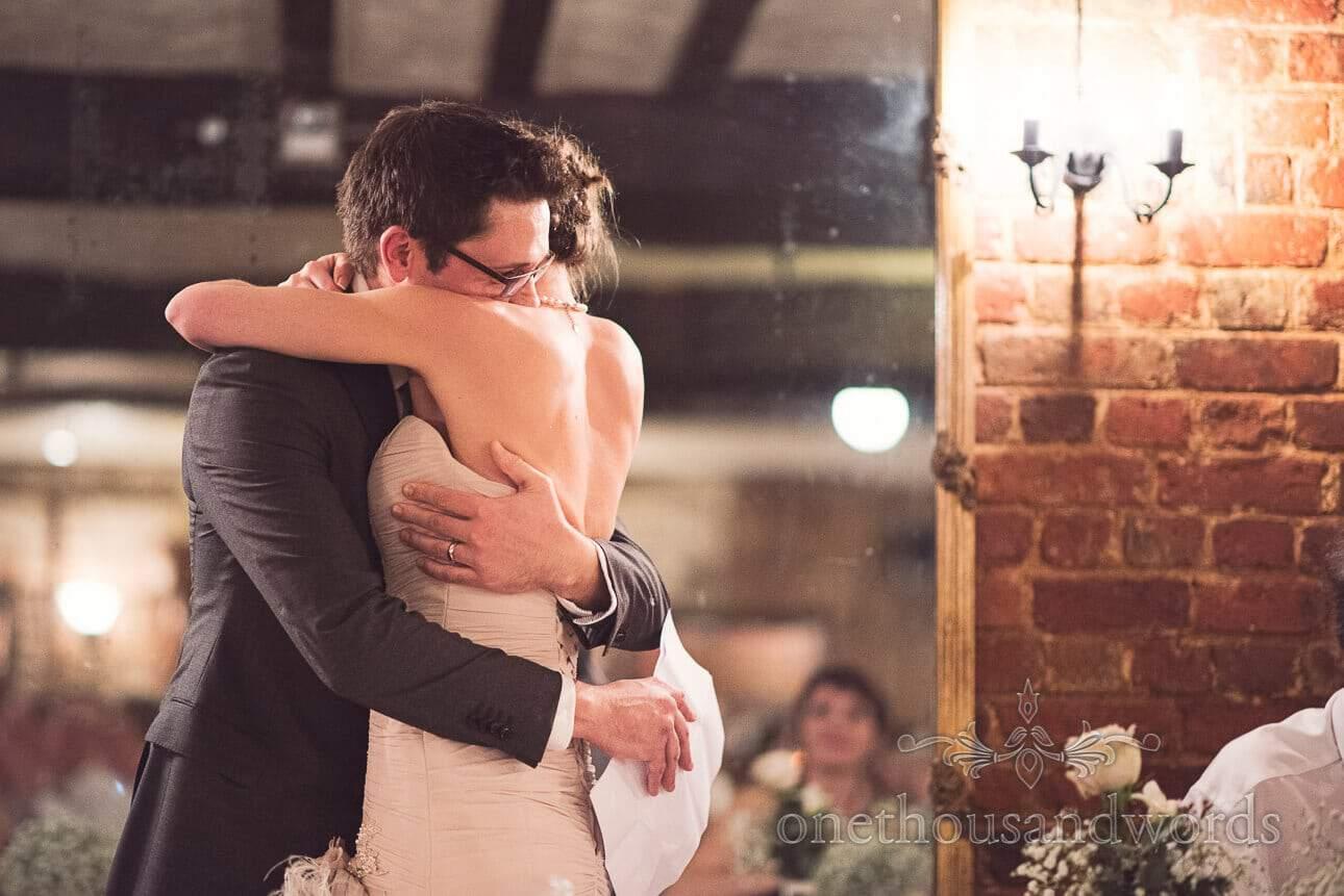 Bride hugs groom during his wedding speech