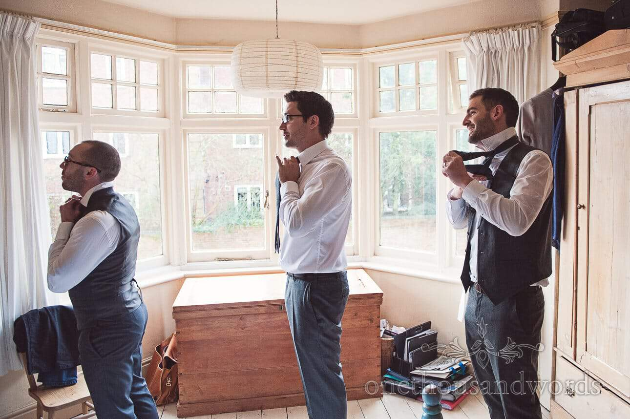 Groom and groomsmen tying ties on wedding morning