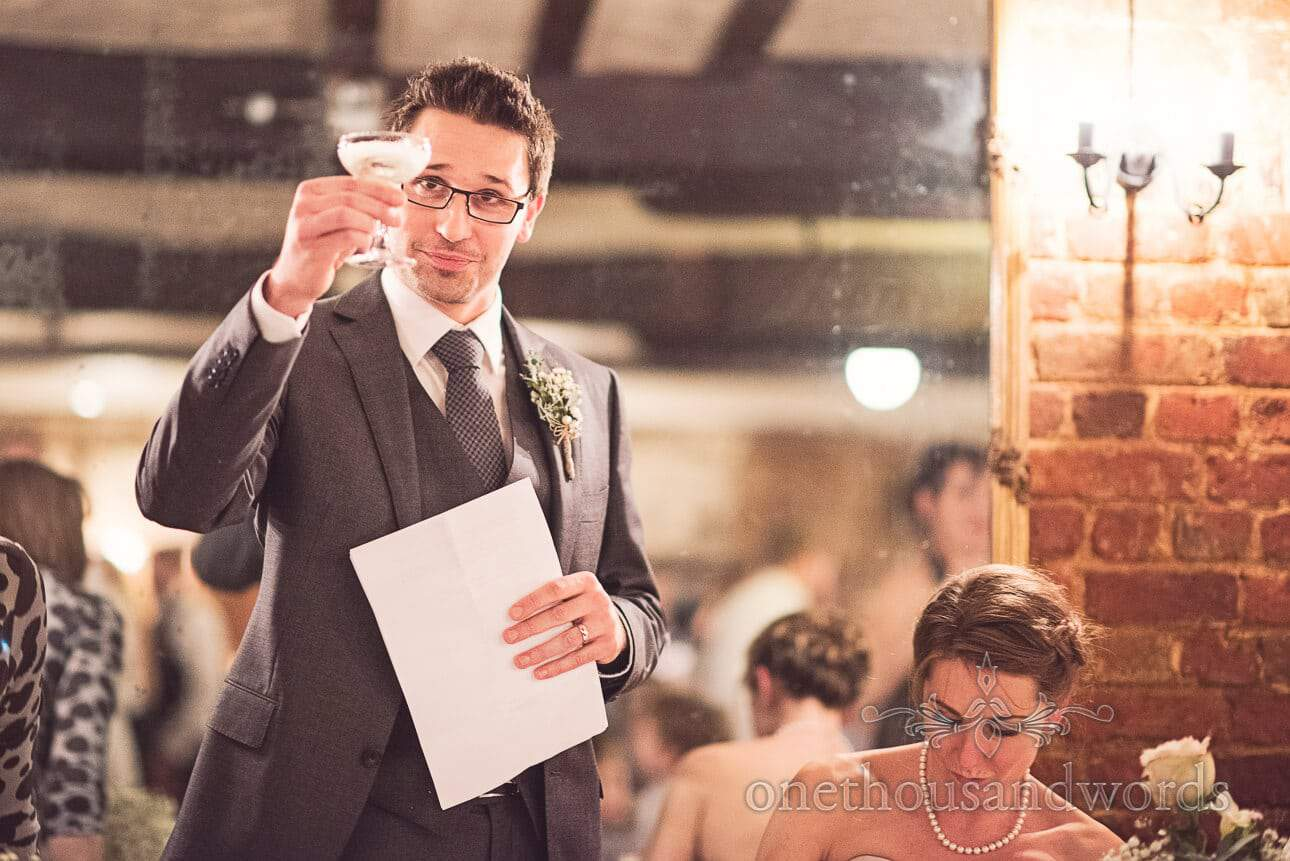 Groom makes champagne toast during wedding speeches