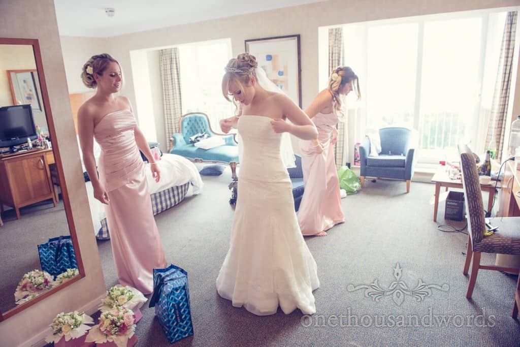 Bride and bridesmaids adjust dresses on wedding morning in Poole hotel