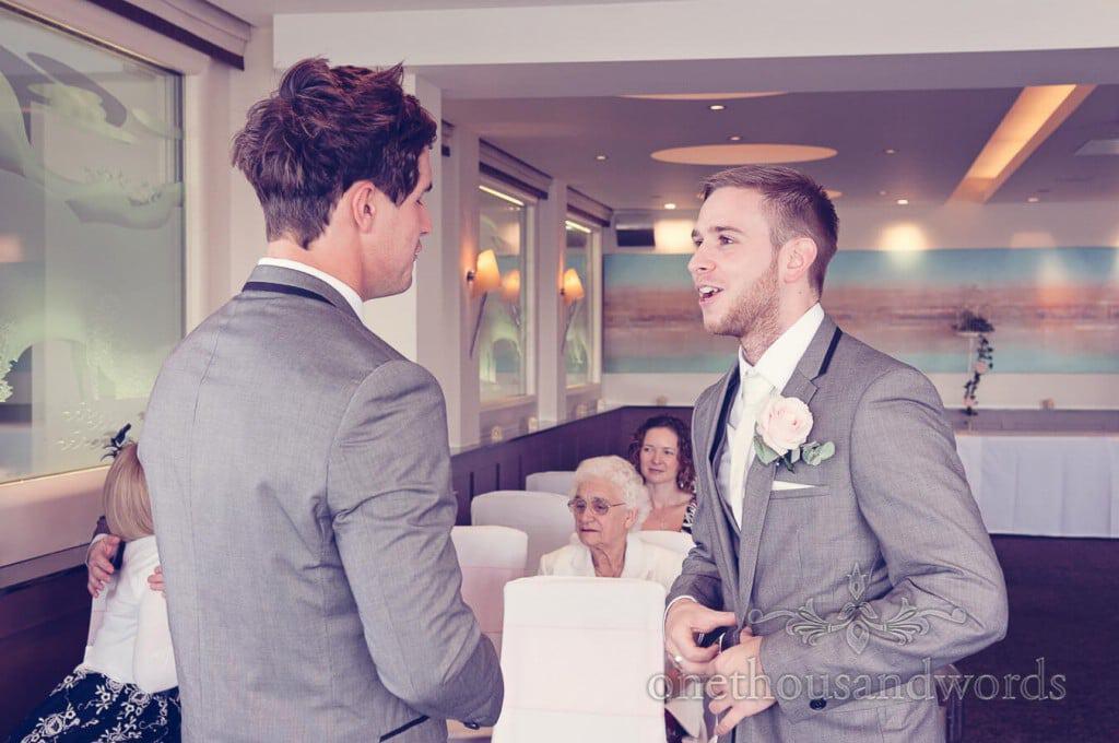 Groom in black trimmed grey wedding suit laughs at hotel wedding