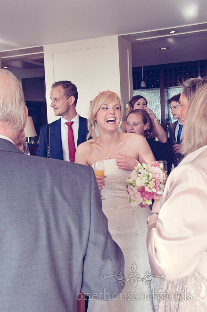 Bride laughing surrounded by weddign guests at drinks reception