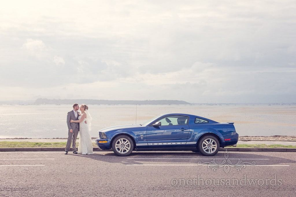 Blue Ford Mustang wedding car with bride and groom in Poole Harbour