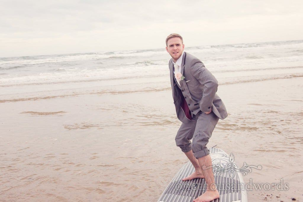 Groom on a surfboard on Dorset beach at Harbour Heights wedding