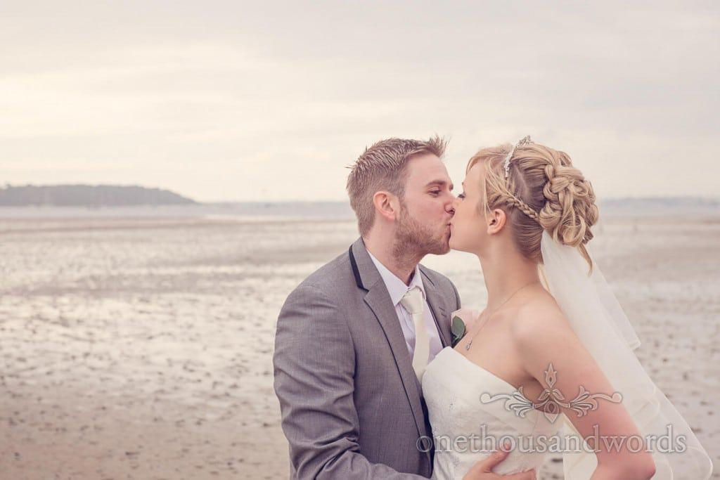 Bride and groom kiss on beach in Poole Harbour