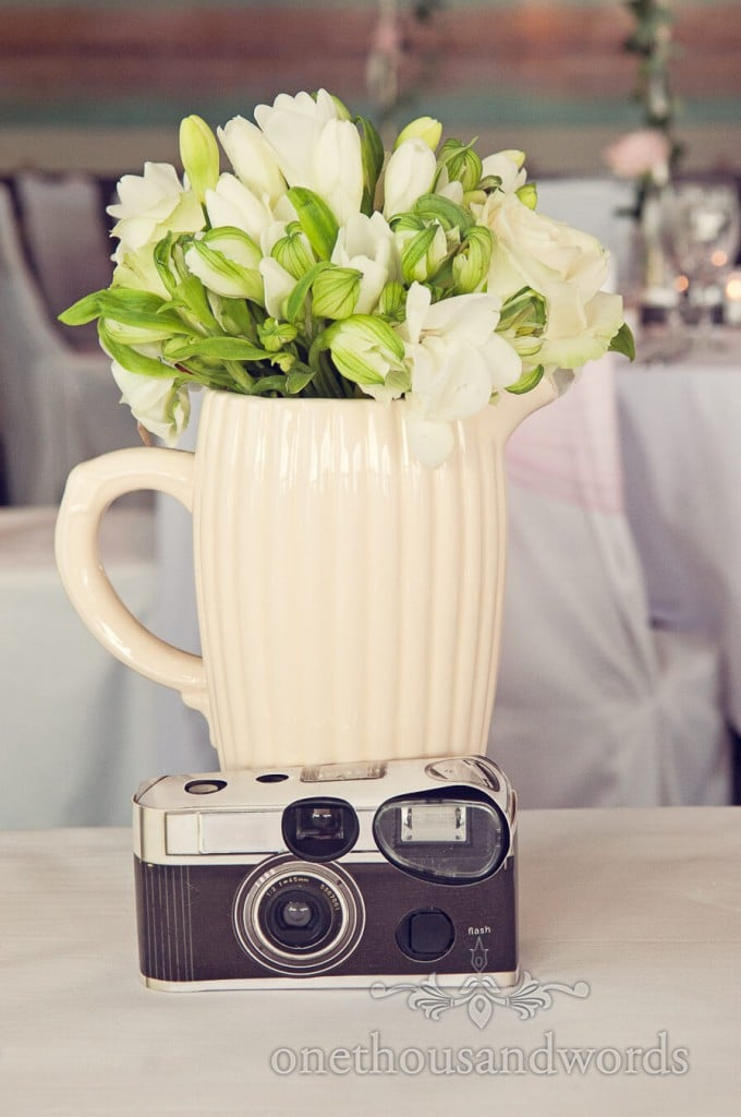 Disposable film camera with white flowers in ceramic jug