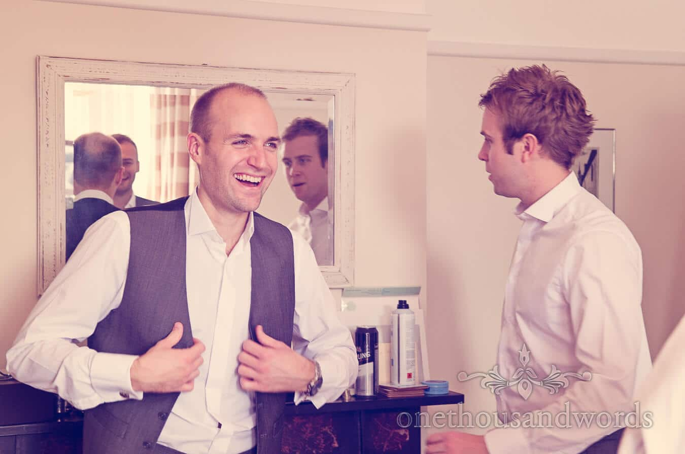 Laughing groom puts on grey waistcoat on wedding morning in Dorset