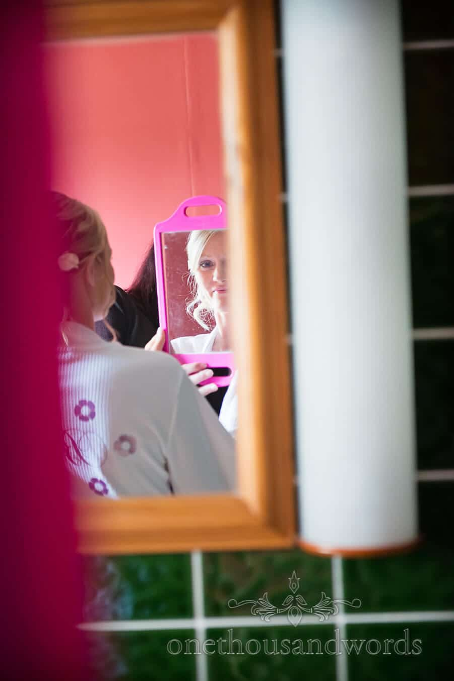 Bride smiles in multiple mirror on wedding morning in Corfe Castle