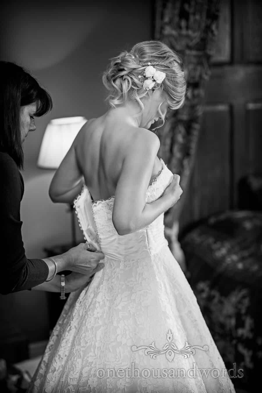 Black and white photograph of bride being zipped into white wedding dress