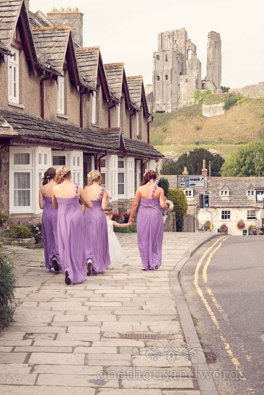 Bridesmaids and flower girl walk towards Corfe Castle in Dorset