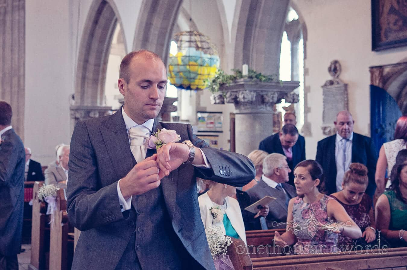 Groom checks his watch waiting for bride in Dorset church wedding ceremony