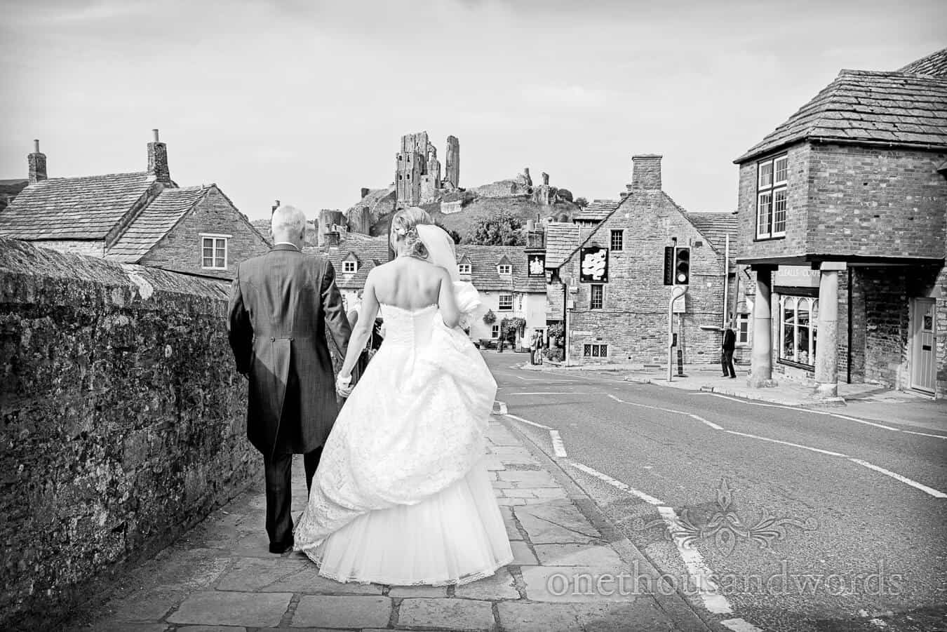 Black and white photo of bride and father walking to Corfe Castle, Dorset