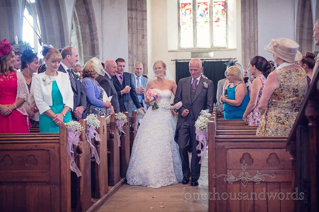 Bride walks down the aisle at St Edwards church in Corfe Castle Dorset
