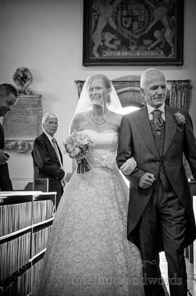 Black and white photograph of bride and father entering church wedding ceremony