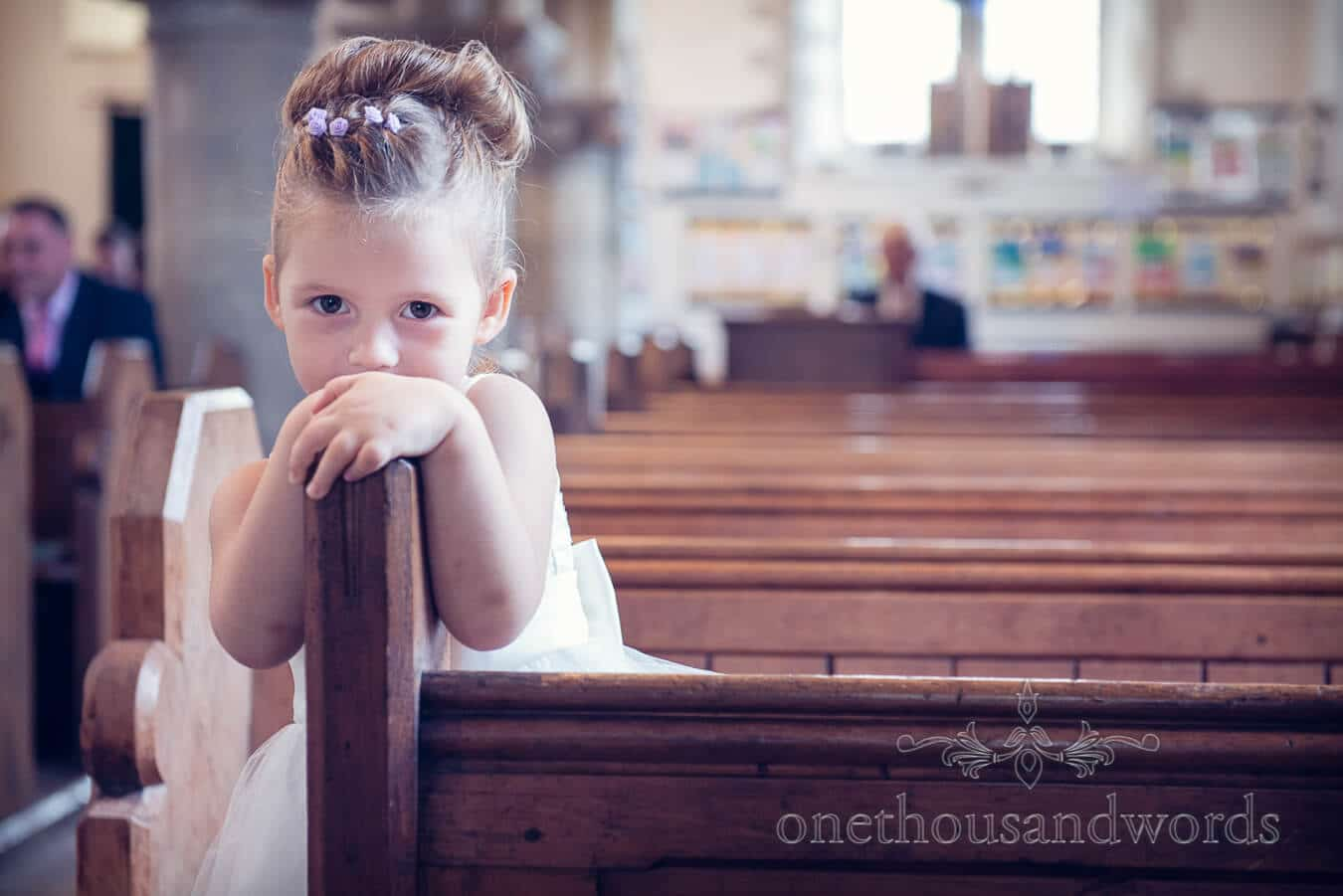 Flower girl looking cute on wooden church aisle in Corfe Castle Dorset