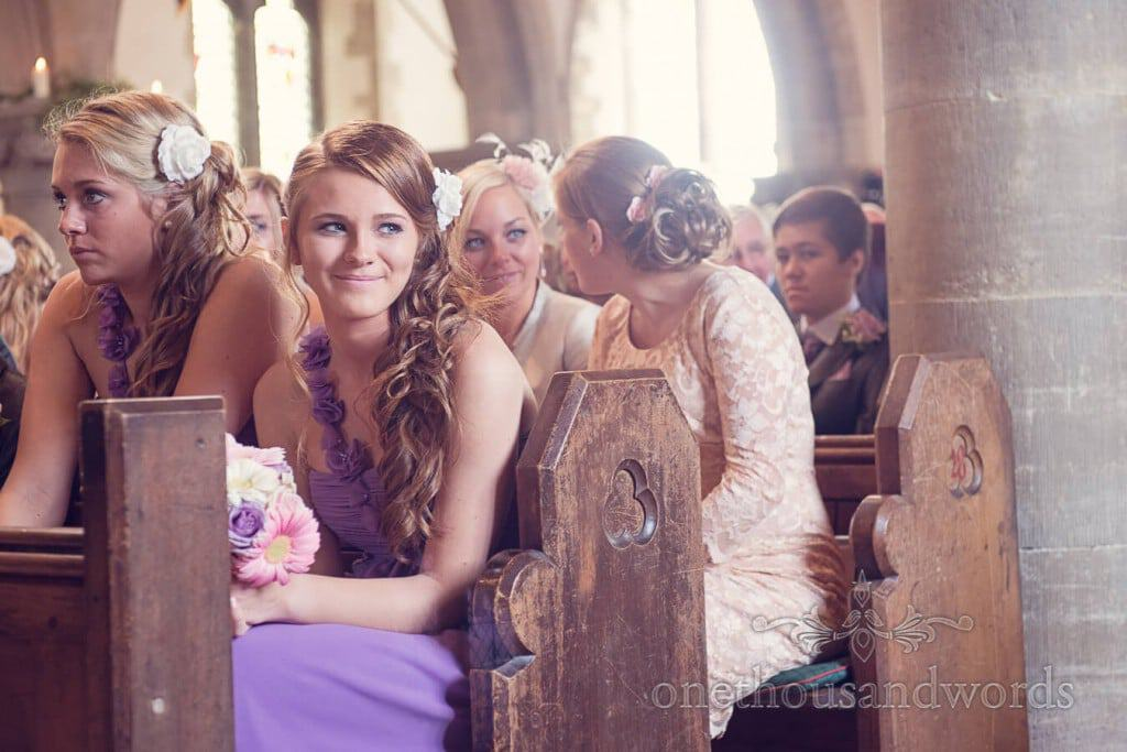 Happy bridesmaid in purple bridesmaids dress sits in wooden church pew