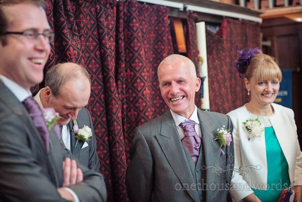 Father of the bride in grey wedding suit laughs during signing the registar