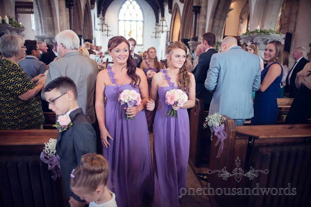 Bridesmaids in purple bridesmaids dresses exit church wedding ceremony