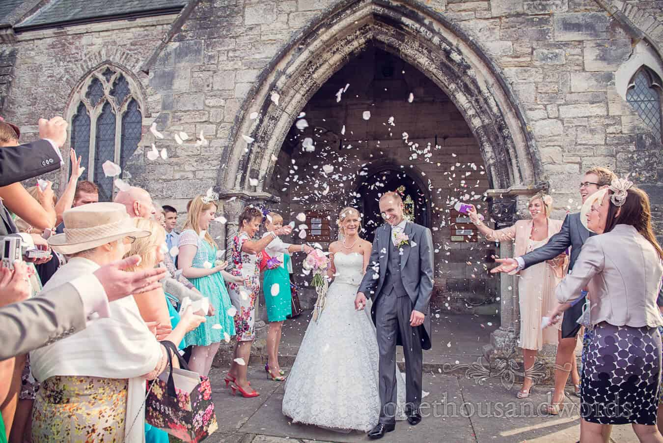 Wedding confetti outside Dorset stone church in Corfe Castle