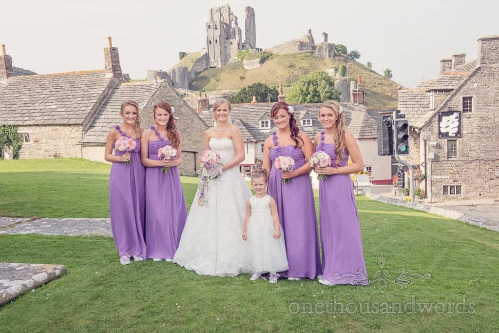 Bride with bridesmaids in purple dresses outside Corfe Castle in Dorset