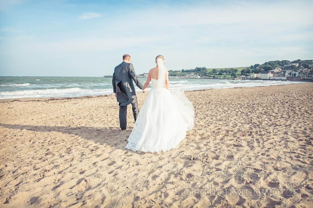 Seaside Wedding Photographs bride and groom walk on Swanage Beach