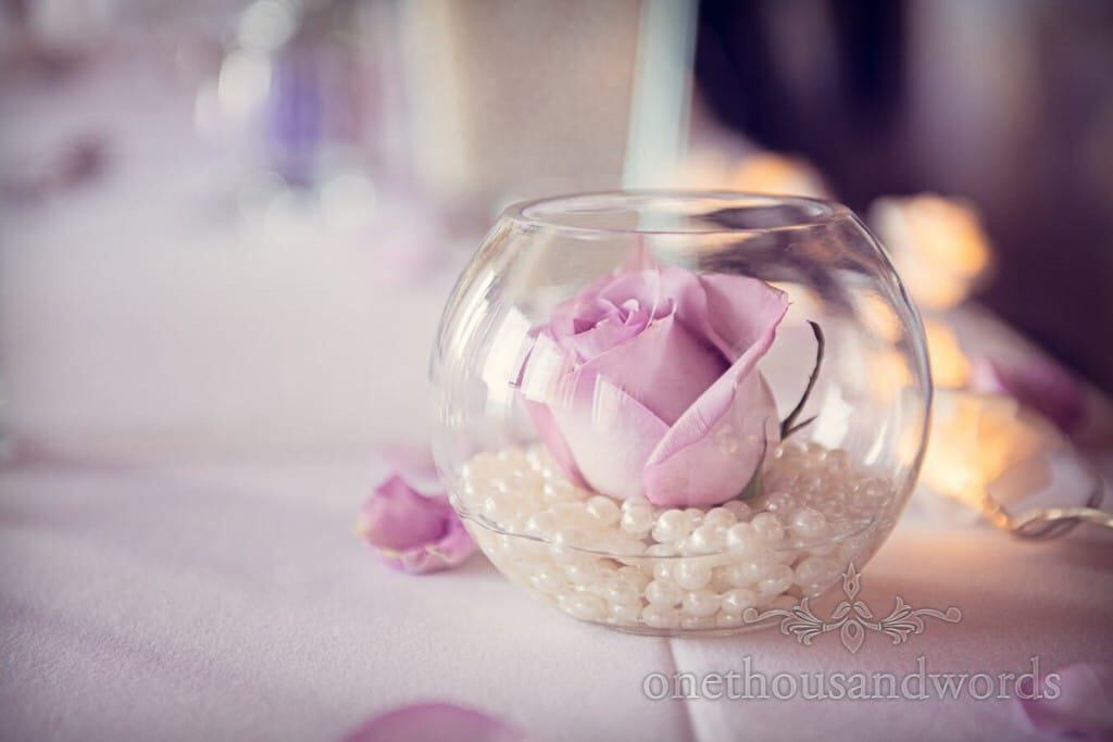Purple wedding flower and white beads in glass bowl decorations