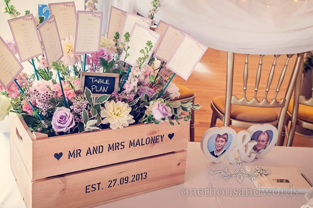 Multi coloursed wedding flowers in customised table plan wedding crate