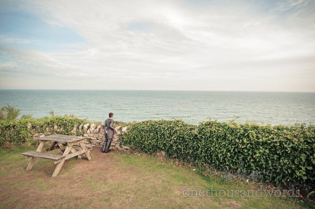 Seaside Wedding Photographs of page boy looking over Dorset sea