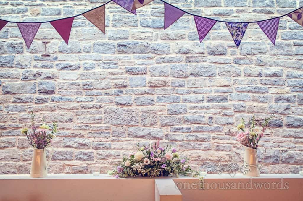 Purple wedding flowers under purple wedding bunting in stone castle