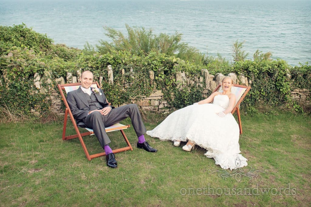 Seaside Wedding Photographs of bride and groom on deck chairs by the sea