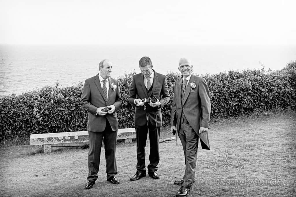 Black and white seaside wedding photographs of wedidng guests in garden