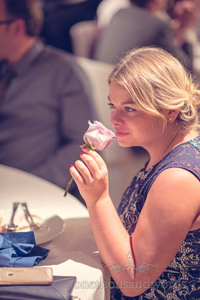 Beautiful blonde wedding guest smells pink rose wedding flower
