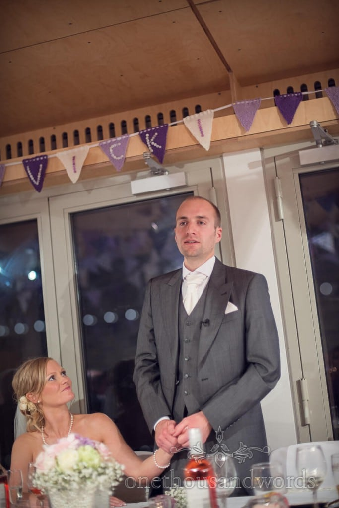 Grooms speech photograph under purple wedding bunting