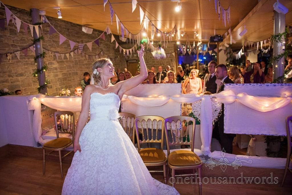 Bride throws bouquet during Seaside Wedding Photographs at Durlston Castle