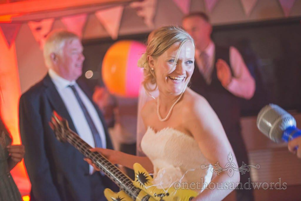 Bride plays inflatable guitar at Durlston Castle wedding evening reception