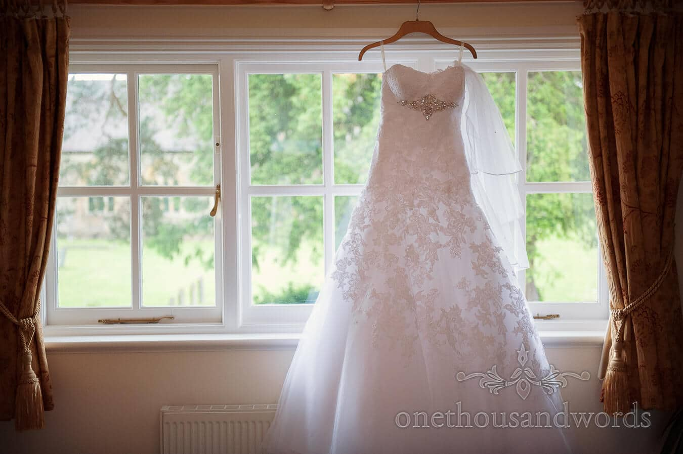 Backlit wedding dress hangs in window at Country Theme Wedding