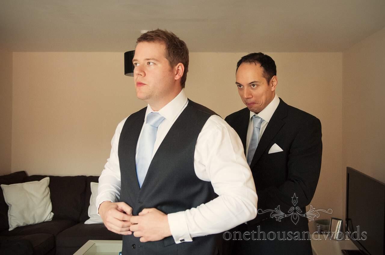Best man dresses a groom on wedding morning