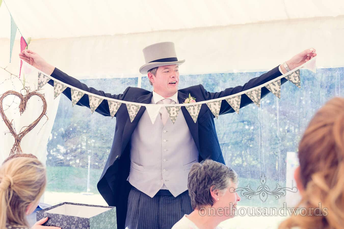 Best man in top hat makes best man's speech with bunting