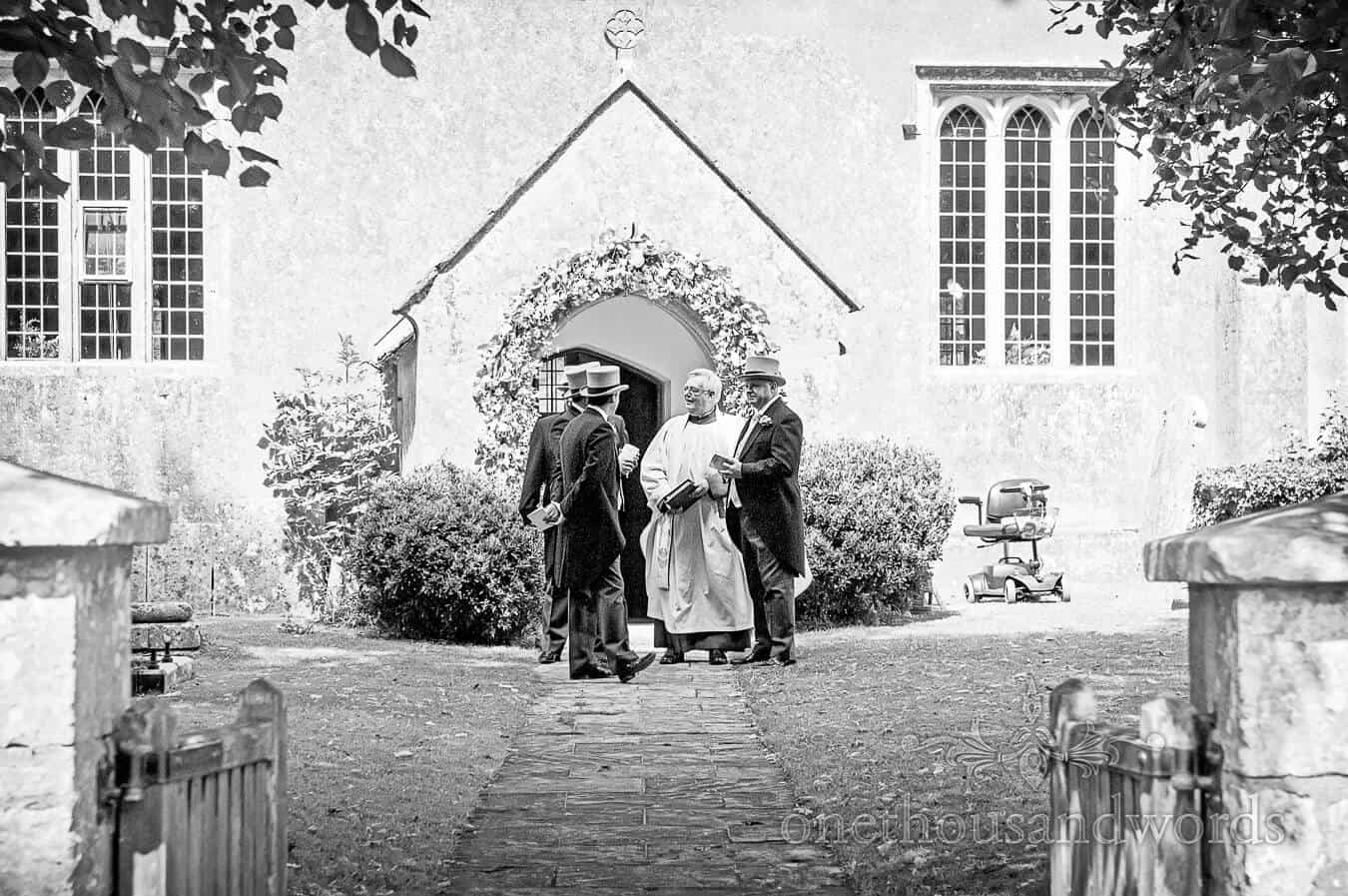 Best men in Top hats talk to vicar at countryside church wedding