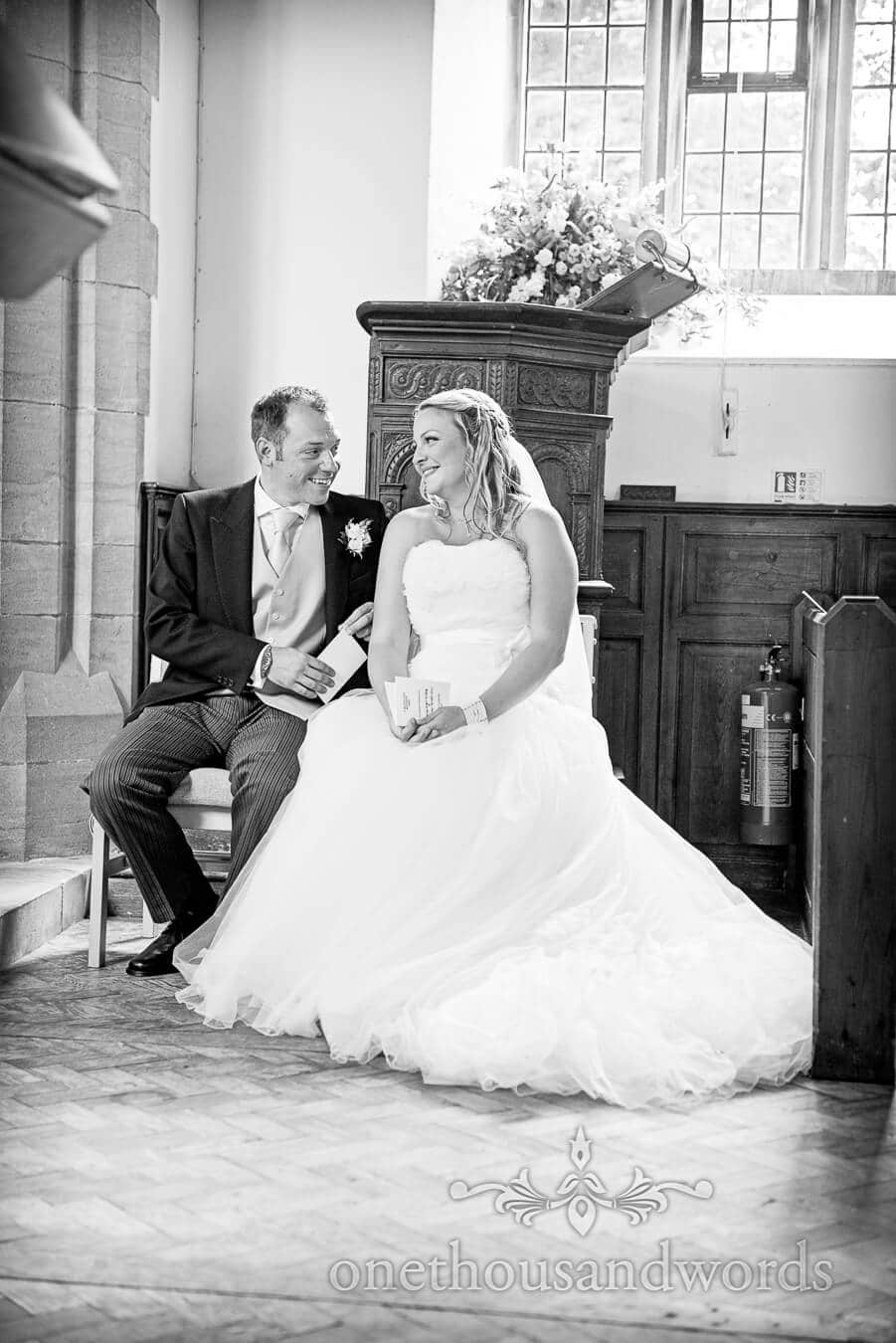 Black and white photograph of bride and groom in church wedding