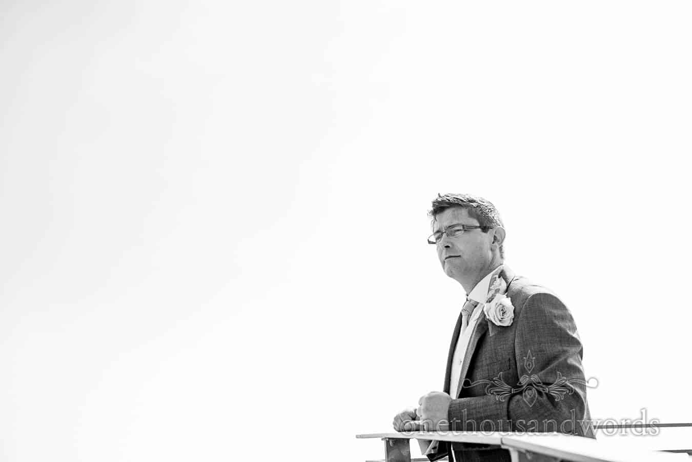 Black and white photograph of groom at wedding looking over sea