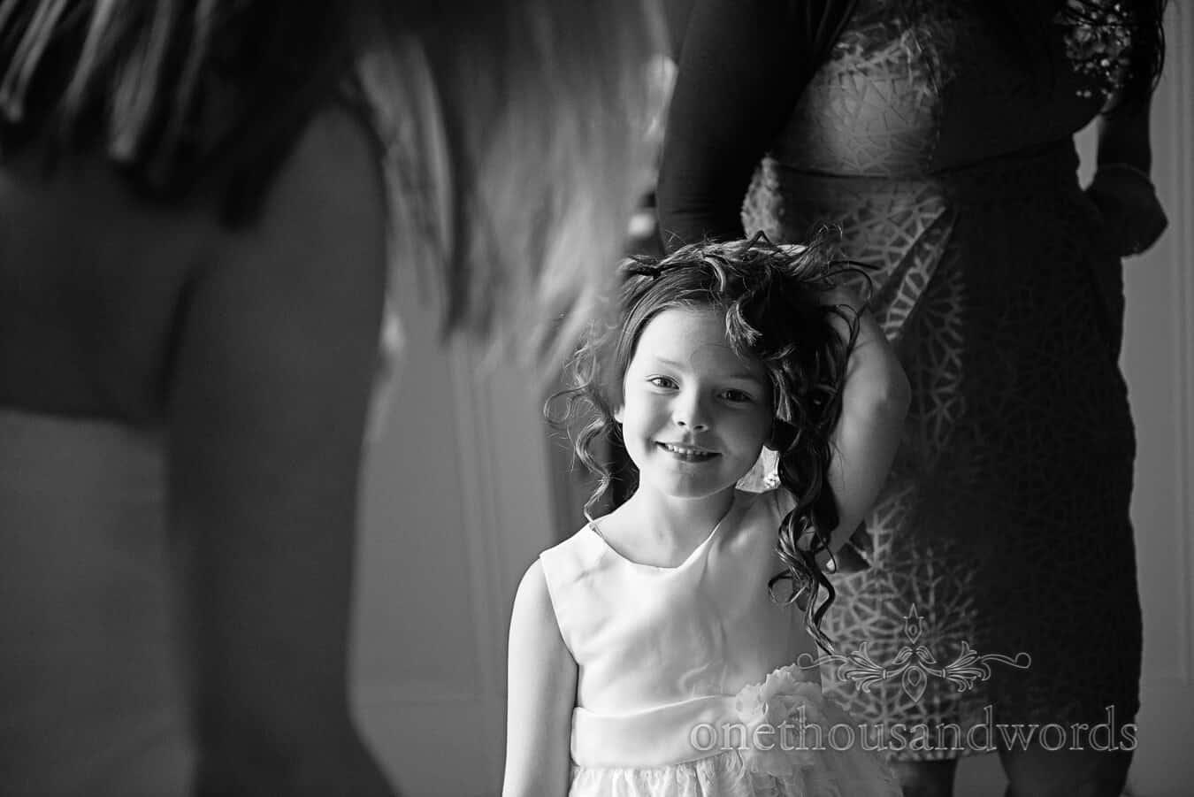 Black and white portrait photograph of flower girl having wedding hair styled