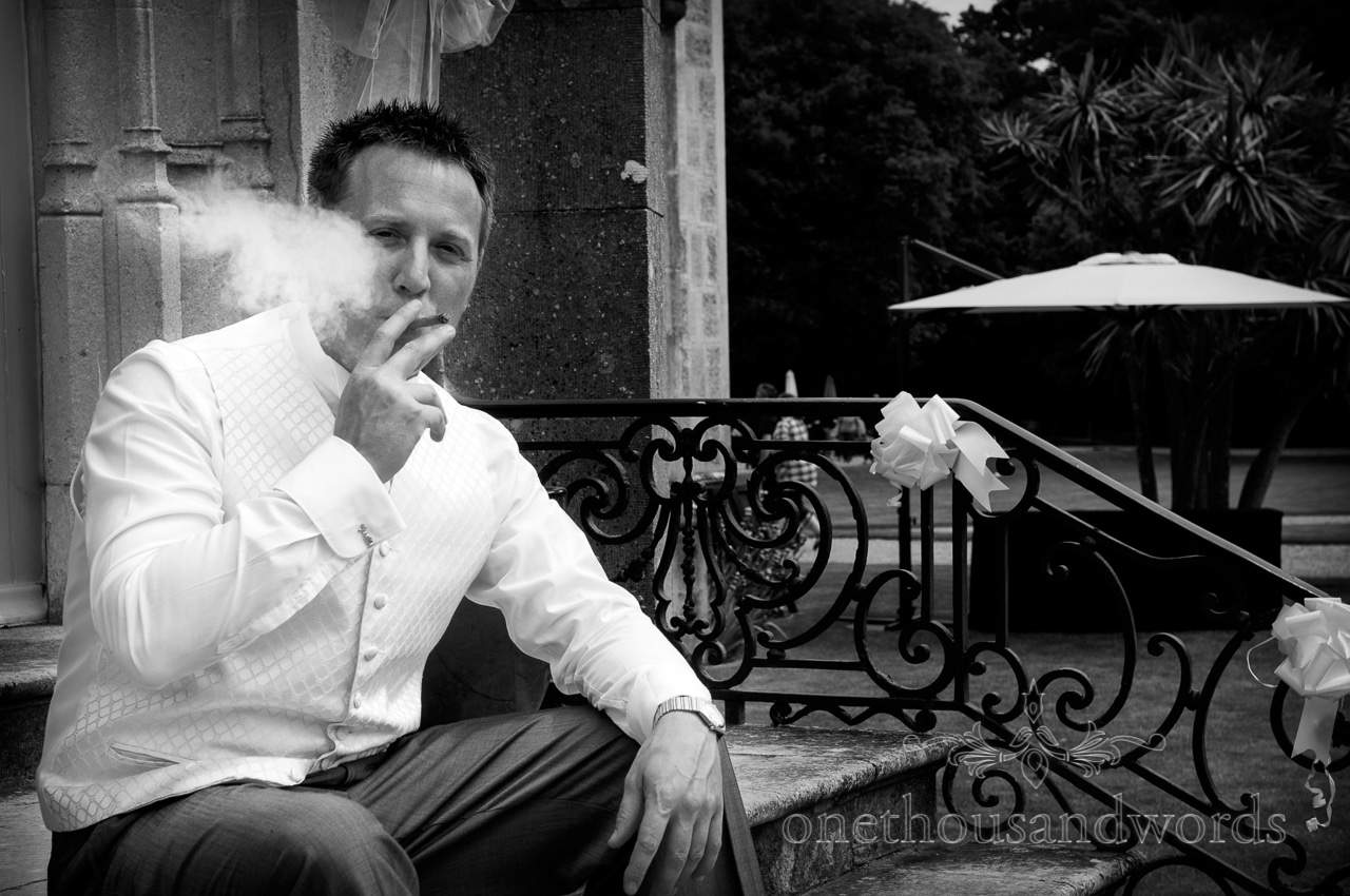 Black and white wedding photograph of groom smoking a cigar
