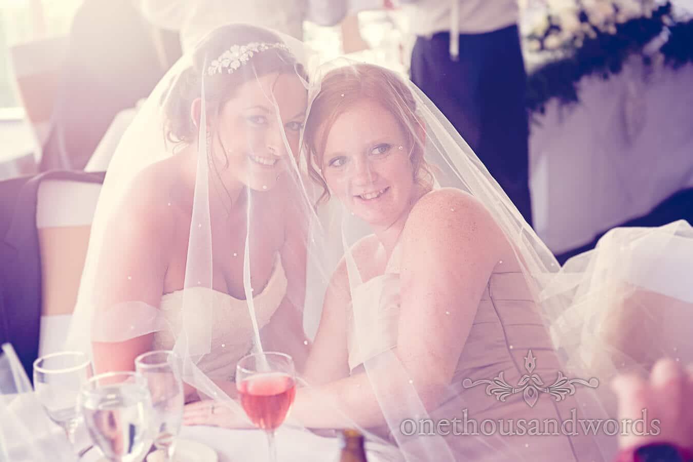 Bride and bridesmaid under wedding veil at Poole wedding venue