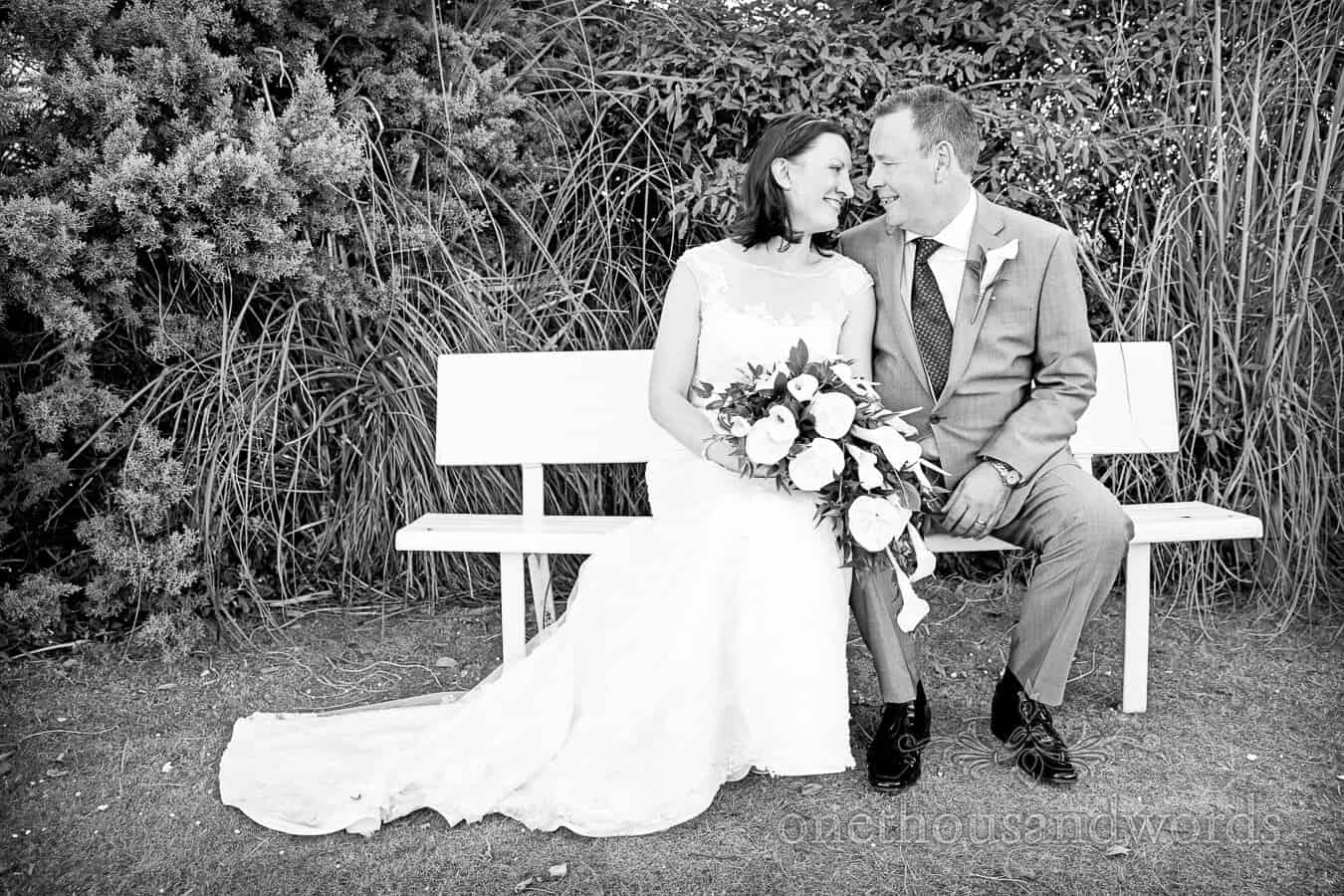 Black and white photograph of bride and groom sat on bench