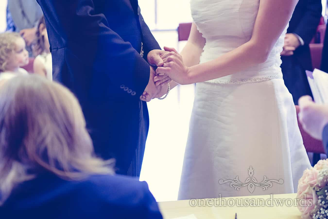 Bride and groom hold hands during countryside wedding ceremony
