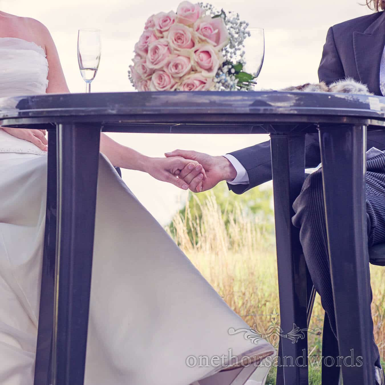 Bride and groom hold hands under table during wedding speeches